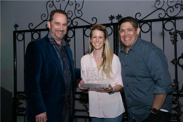 Kristen Briggs holding a Neopost Award